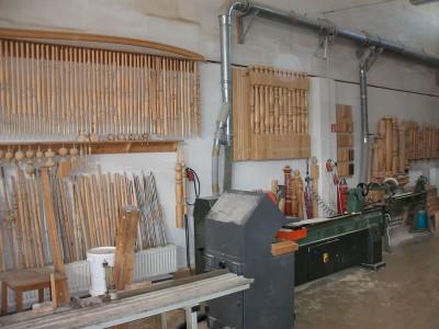 Werkhalle mit an der Wand aufgereihten Sprossen und Pfosten für Holztreppen